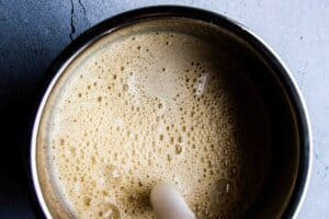 Blending the oat milk eggnog with the hand blender.