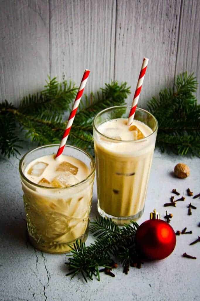 Two glasses of oat milk eggnog with Christmas decorations.