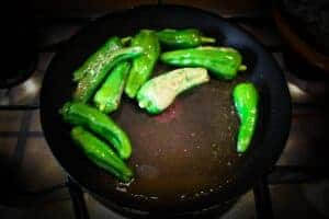 Blistering the peppers in a pan.