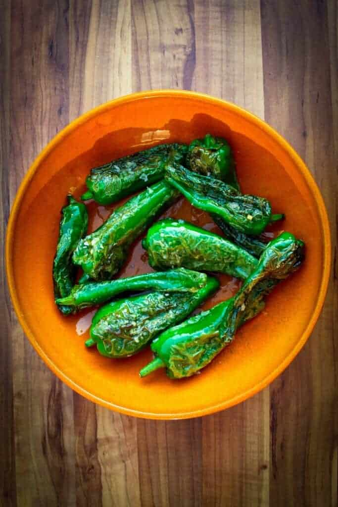 Padron peppers with ginger and garlic in a bowl.