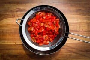 Tomatoes curing over a strainer.