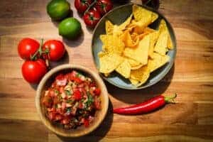Pico de gallo, tortilla chips, chili, tomato and fresh limes on the table.