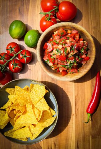 Pico de gallo, tortilla chips, chili, tomato and fresh limes on the table.