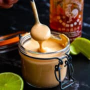 Spicy mayo in a small mason jar with a spoon.