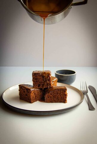 Sticky toffee pudding on a plate with salted caramel sauce drizzling over top.