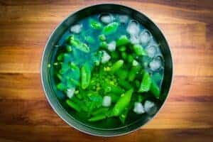 Refreshing the peas in ice water.