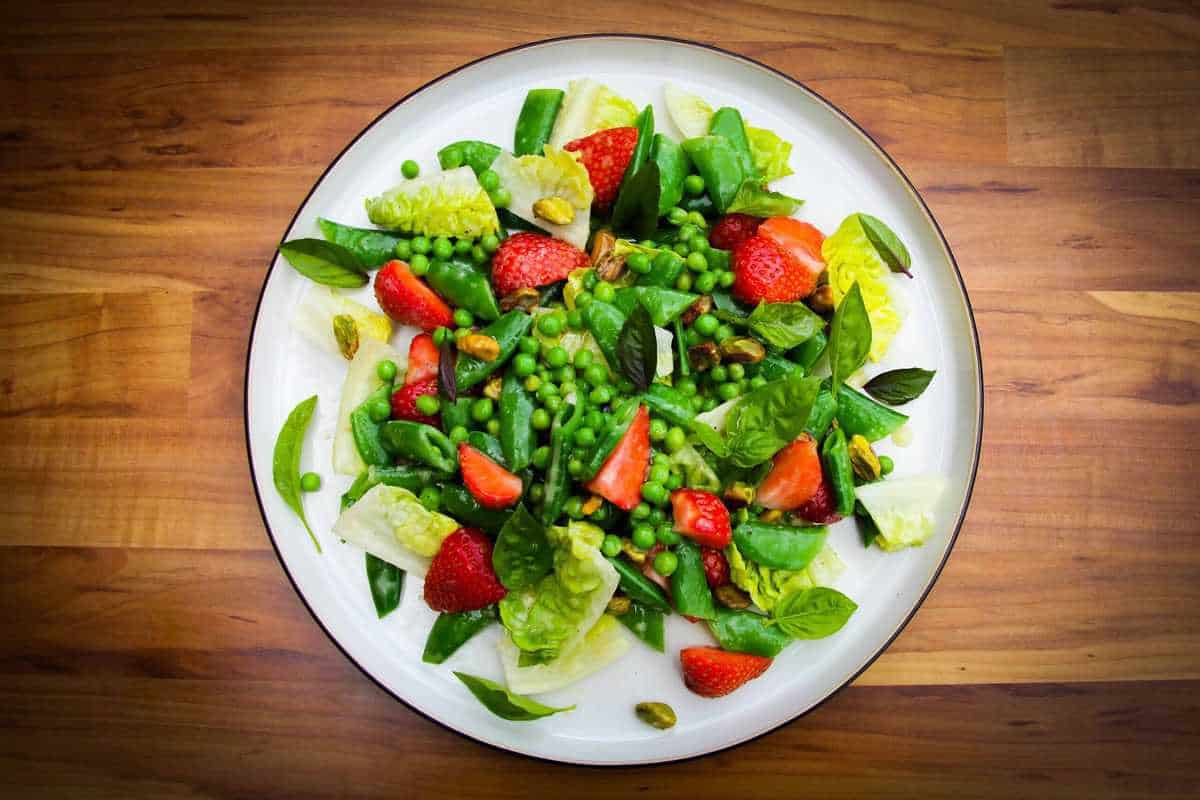 Strawberry pea and basil salad on a plate.