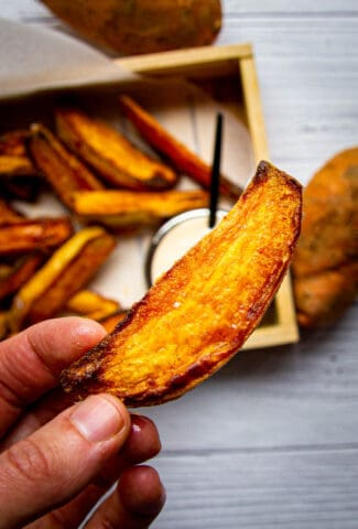 Crispy sweet potato wedges with spicy mayo in the background.