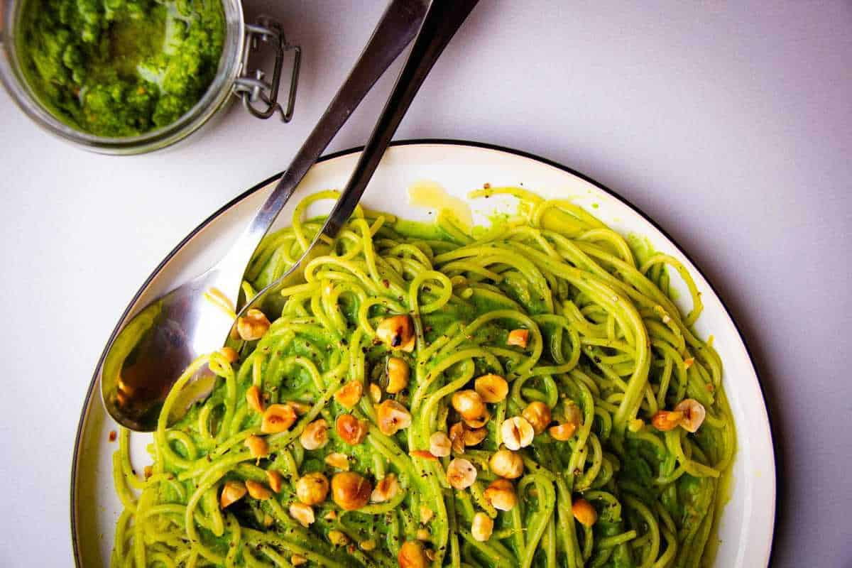 Vegan Pasta Pesto Spaghetti with hazelnuts, sweet pea and miso on a fork over a plate.