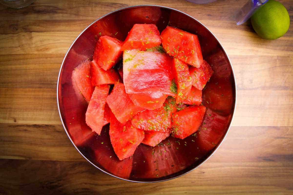 The watermelon, lime and vodka in a bowl ready to blend.