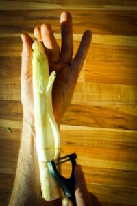 Peeling the white asparagus from top to bottom in long strokes.