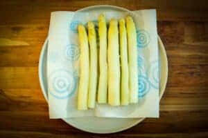 Drying the white asparagus on a plate with paper towel.