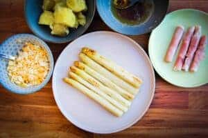White asparagus on a table with rolled ham, boiled potatoes, brown butter and chopped egg.