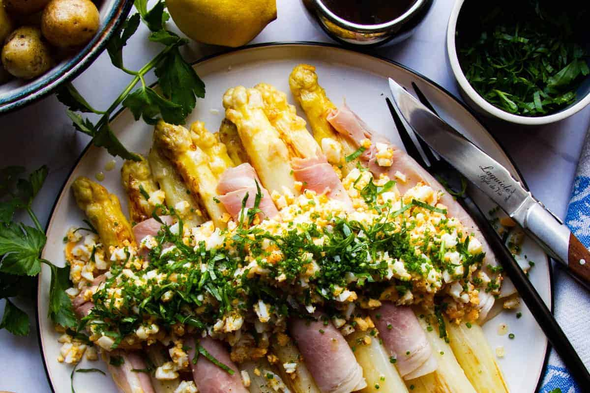 White asparagus with ham, egg, potato, chives, parsley and brown butter.