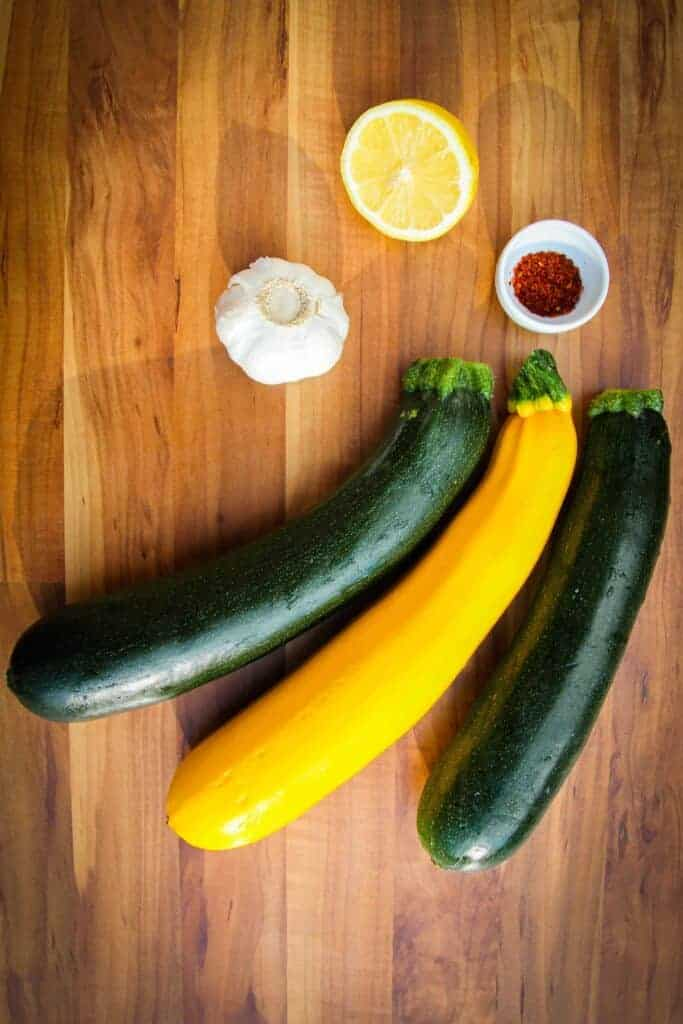 Raw zucchini, chili, lemon and garlic on the table.