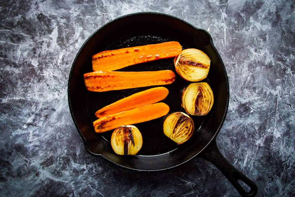 Frying the onions and carrots in a cast iron pan.