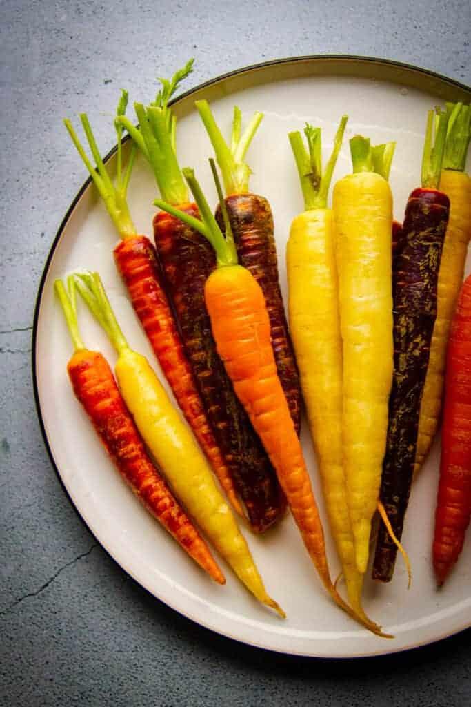 Raw rainbow carrots on a big plate, not peeled.