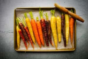 The rainbow carrots lined up on a tray with oil and salt.