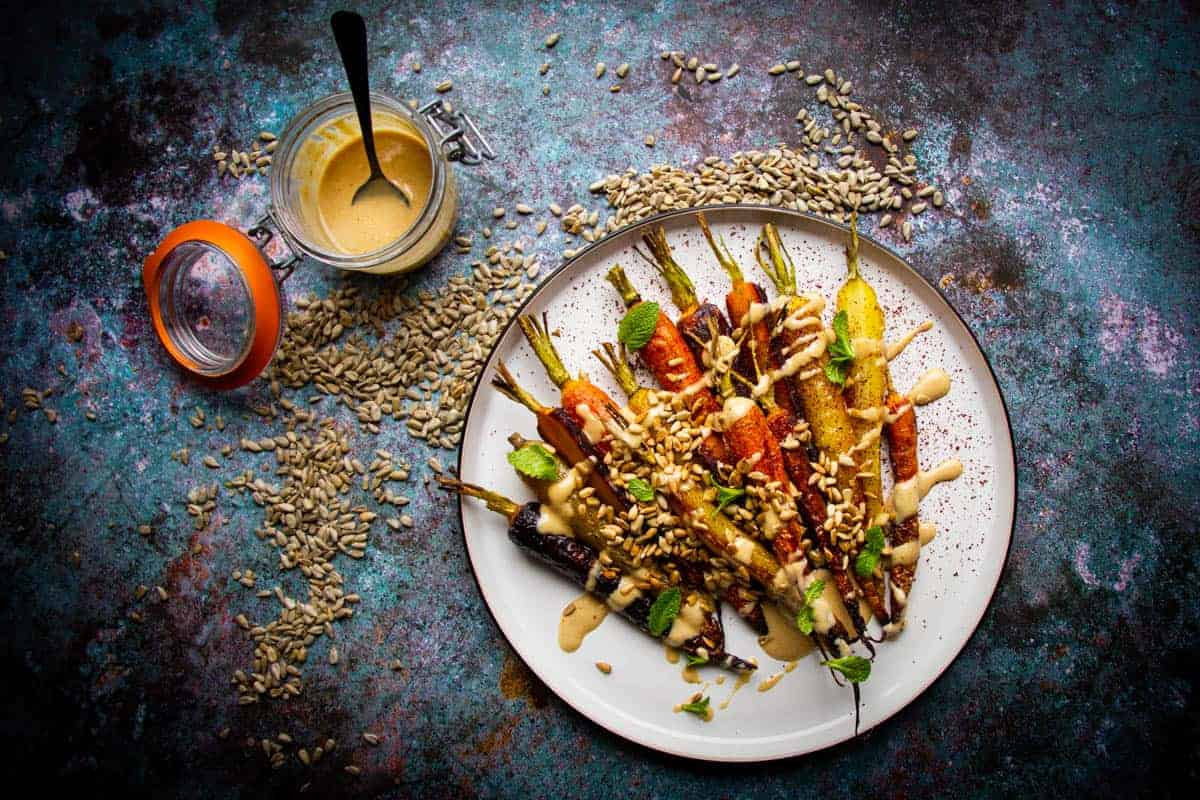 Roasted rainbow carrots on a plate with a toasted sunflower dressing on the side.