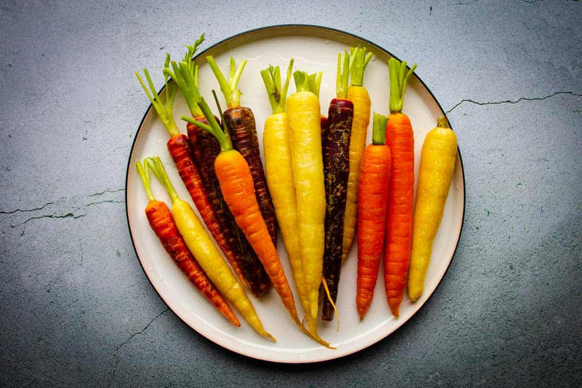 The raw rainbow carrots cleaned on a plate.