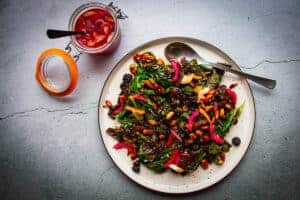 sauteed rainbow chard with brown butter raisins, almonds and chili on a plate with pickled chard stem on the side.