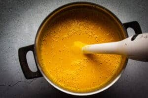 Blending the soup with a hand blender until smooth.