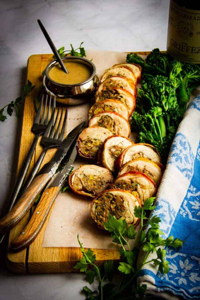 Stuffed chicken leg with bacon, herbs, porcini, walnut and a date sauce on a board with wine and broccoli.