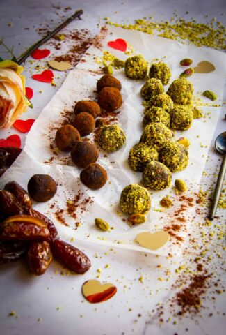 Rolled vegan chocolates in pistachio and cocoa powder.