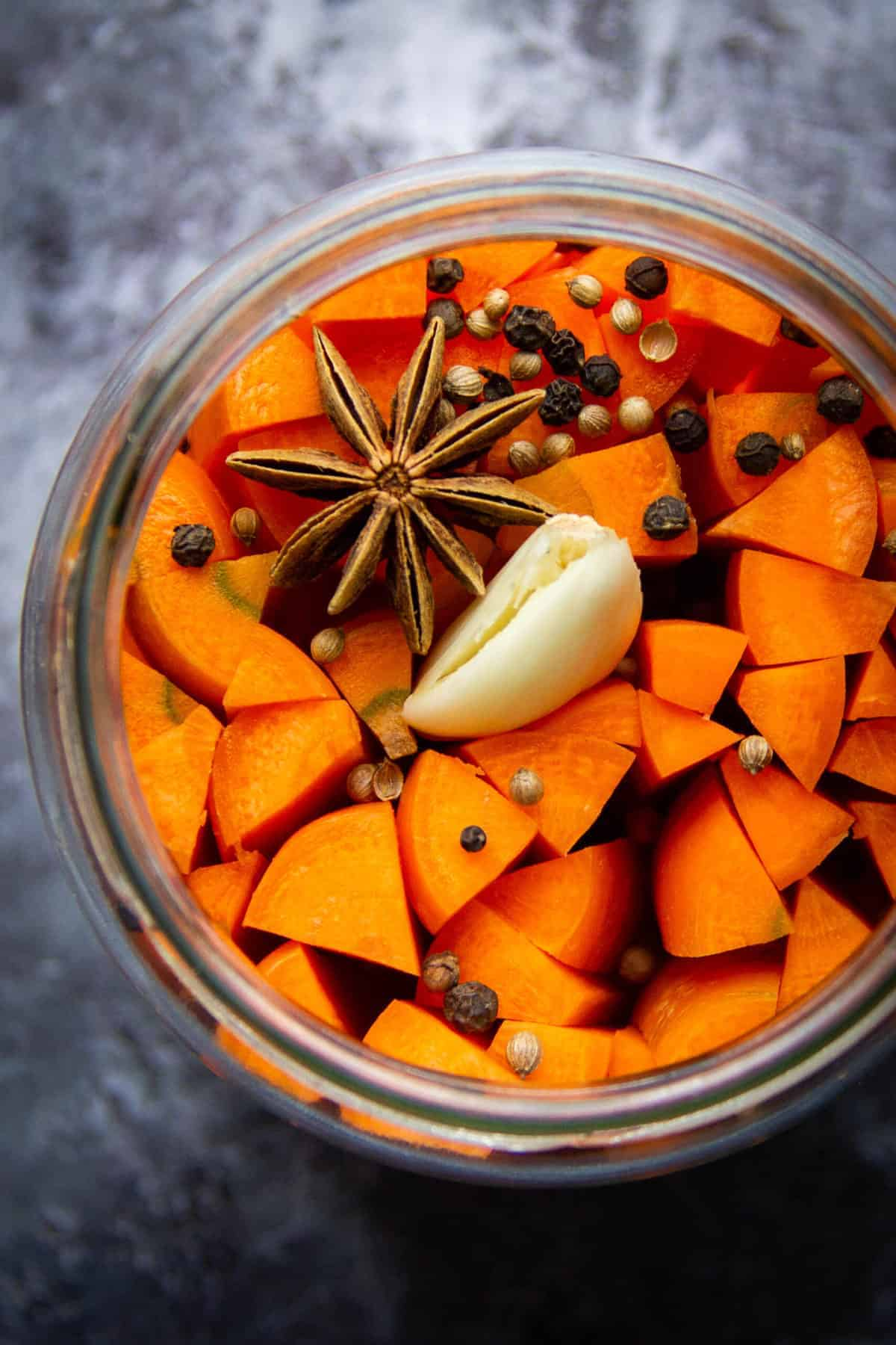 Fermented carrots in a mason jar with spices.