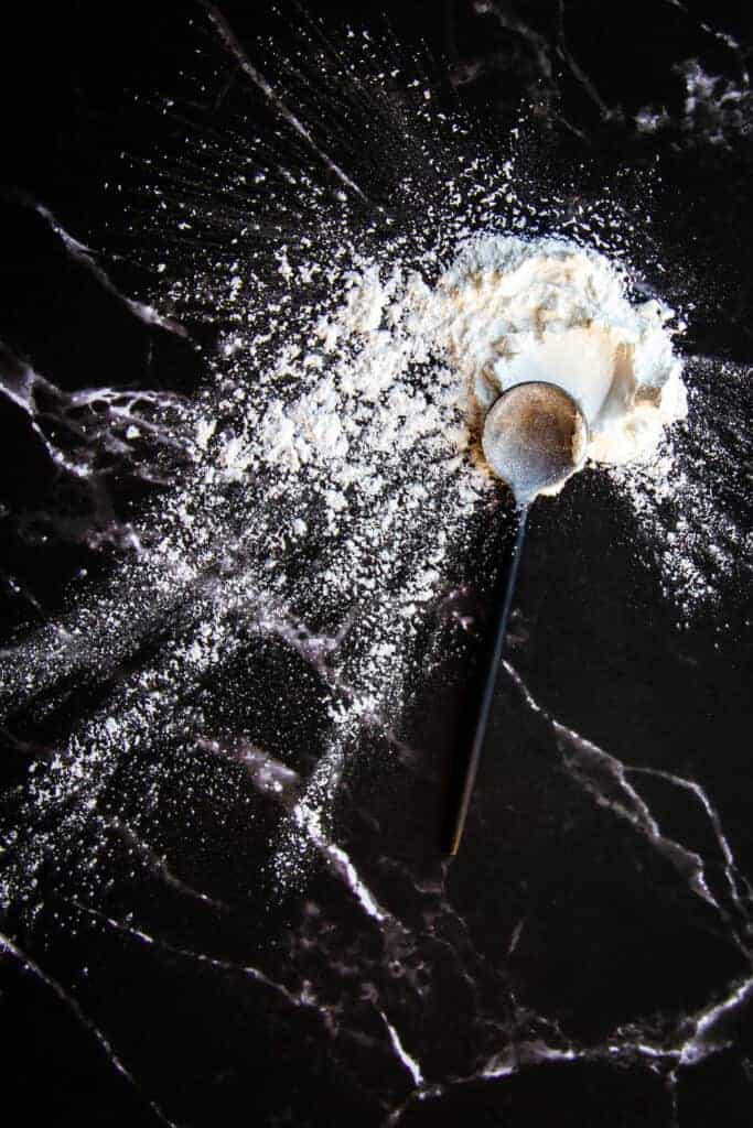 Arrowroot powder on a marble table with a spoon.