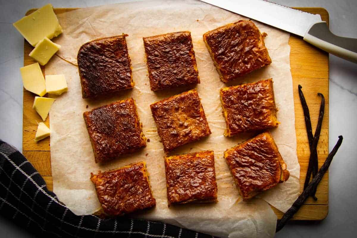 The finished vanilla brownies cut into 9 squares on a board.