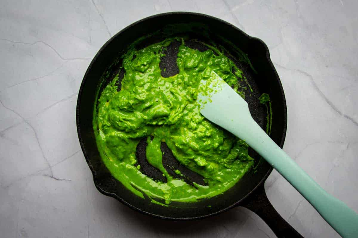Mixing the green eggs in a cast iron skillet pan.