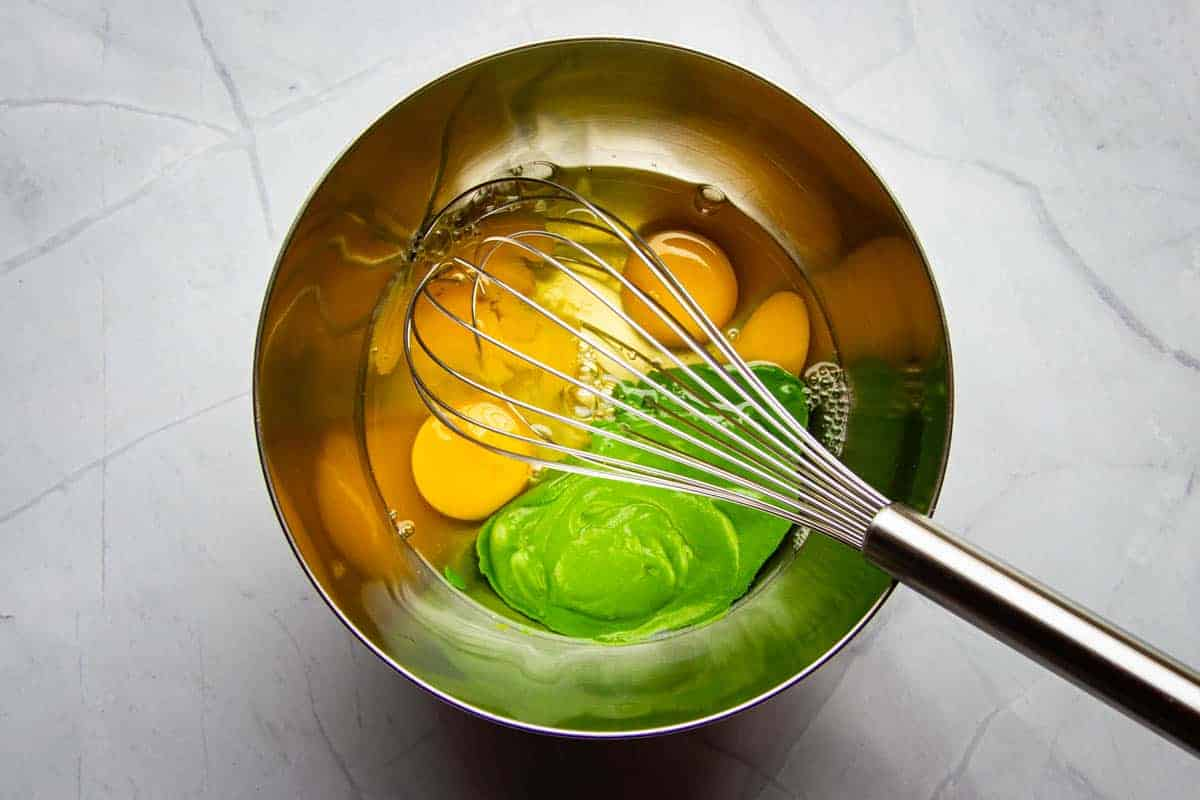 Adding the spinach puree to the eggs in a bowl.