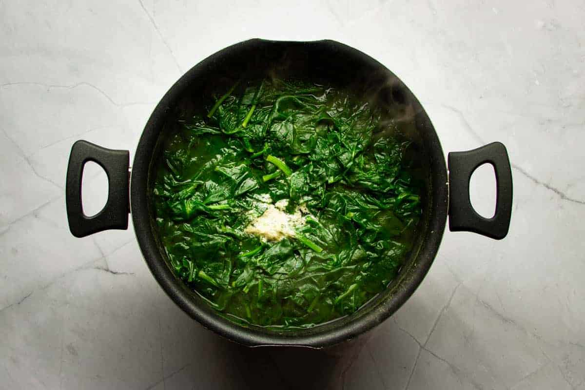Boiling the spinach in a large pot of salted water.