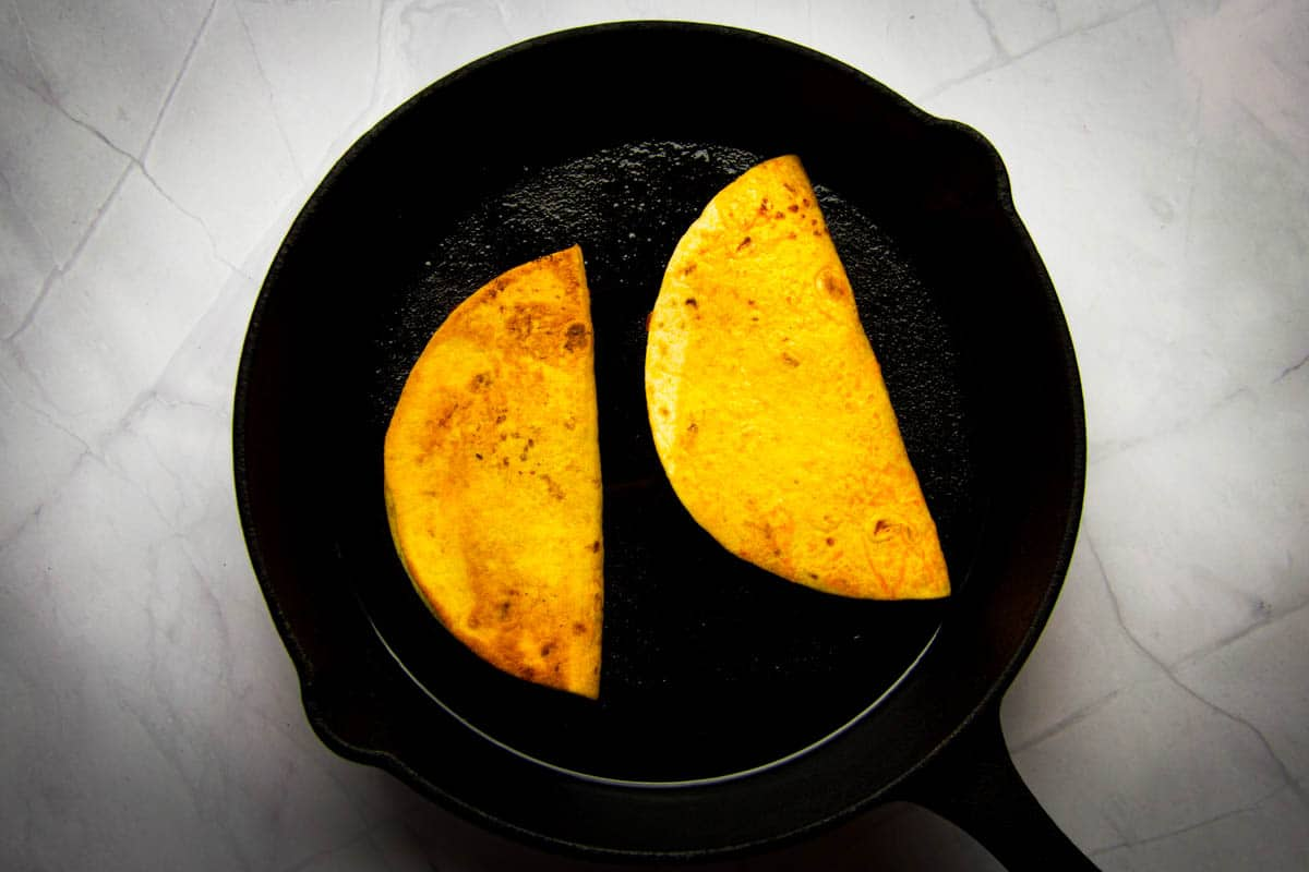 Frying the tacos in a cast iron pan.