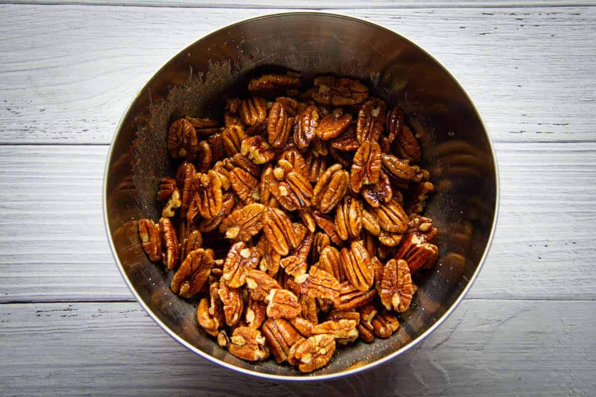 tossing the pecans in butter, chili, cinnamon and salt