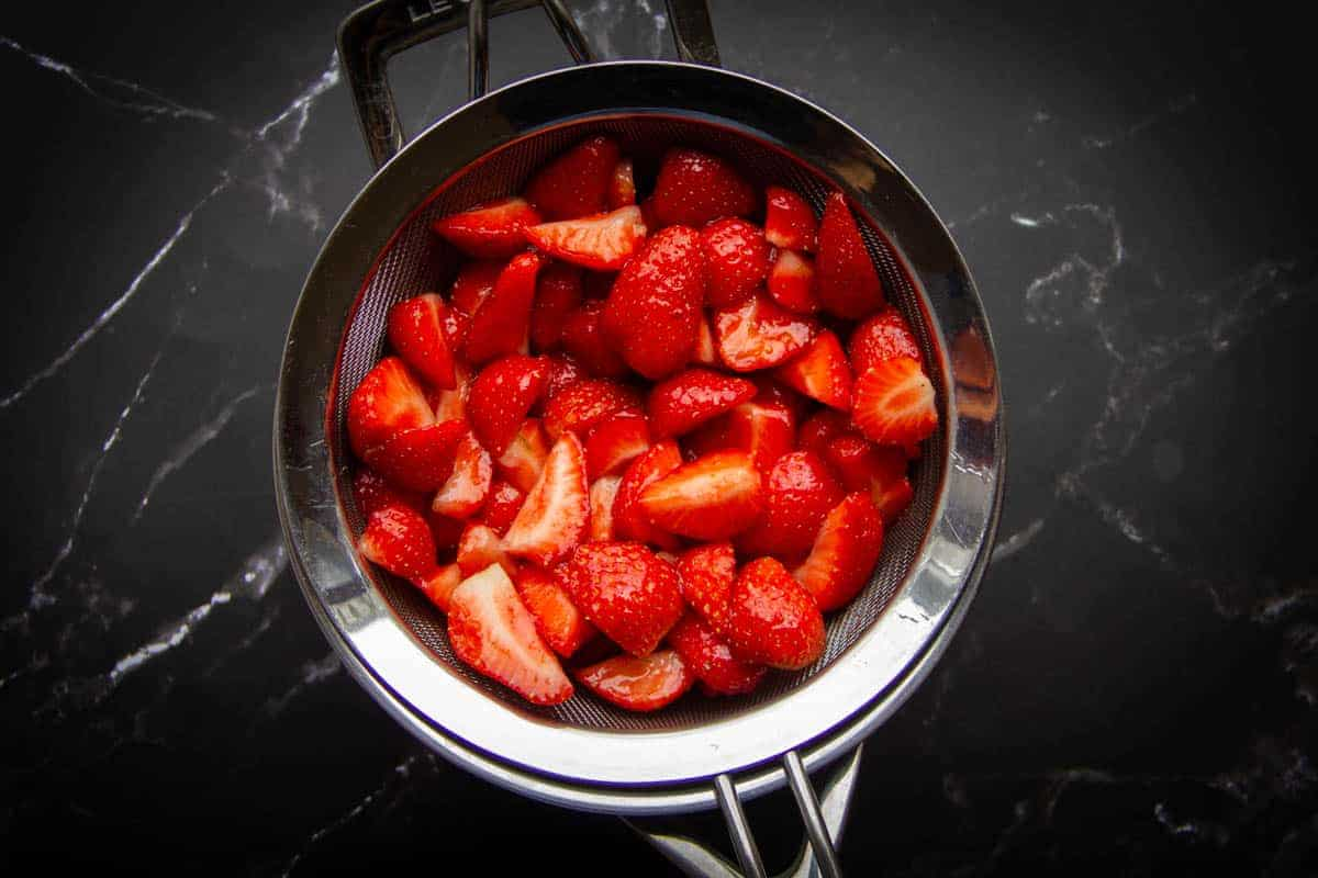 Straining the cured strawberries