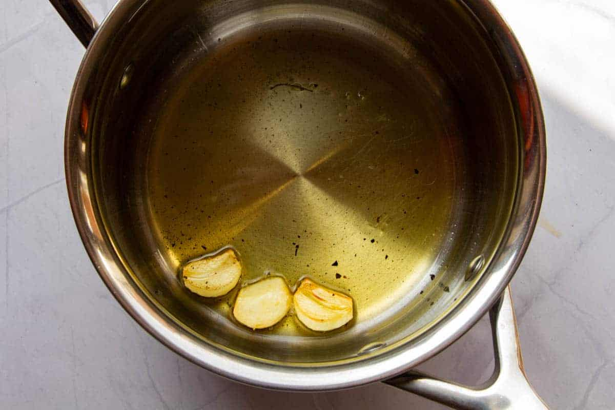 Toasting the peeled garlic in the oil.