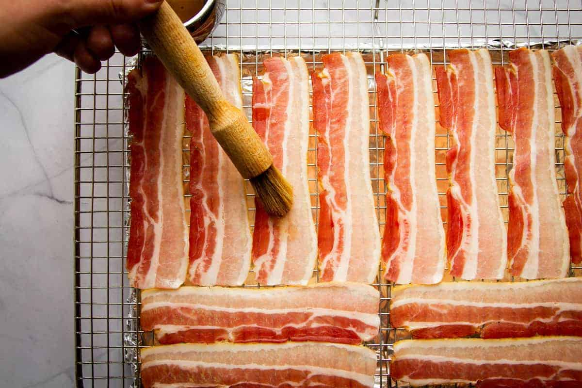 Brushing the bacon with maple syrup.
