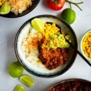Sofritas in a bowl with guac, beans, corn and fresh lime.