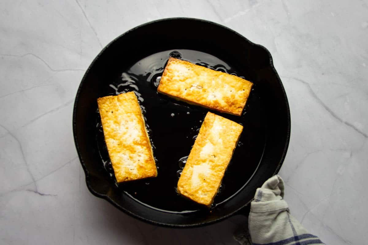Searing the tofu in a cast iron pan until golden brown.