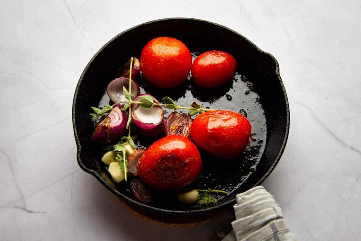 Frying the oregano and garlic in the same pan.