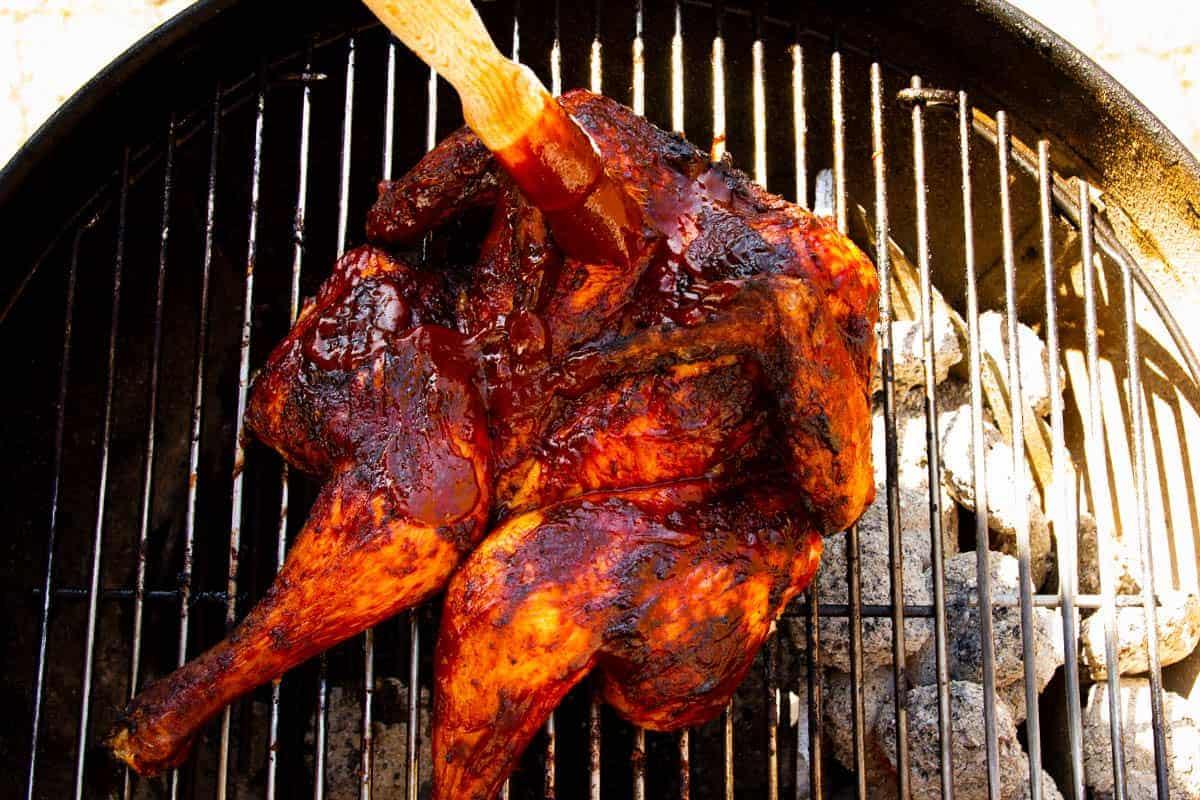 Brushing the bird with bbq sauce.