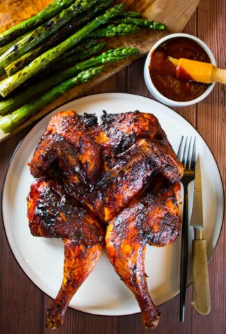 Grilled spatchcock chicken with bbq sauce and asparagus on the side.