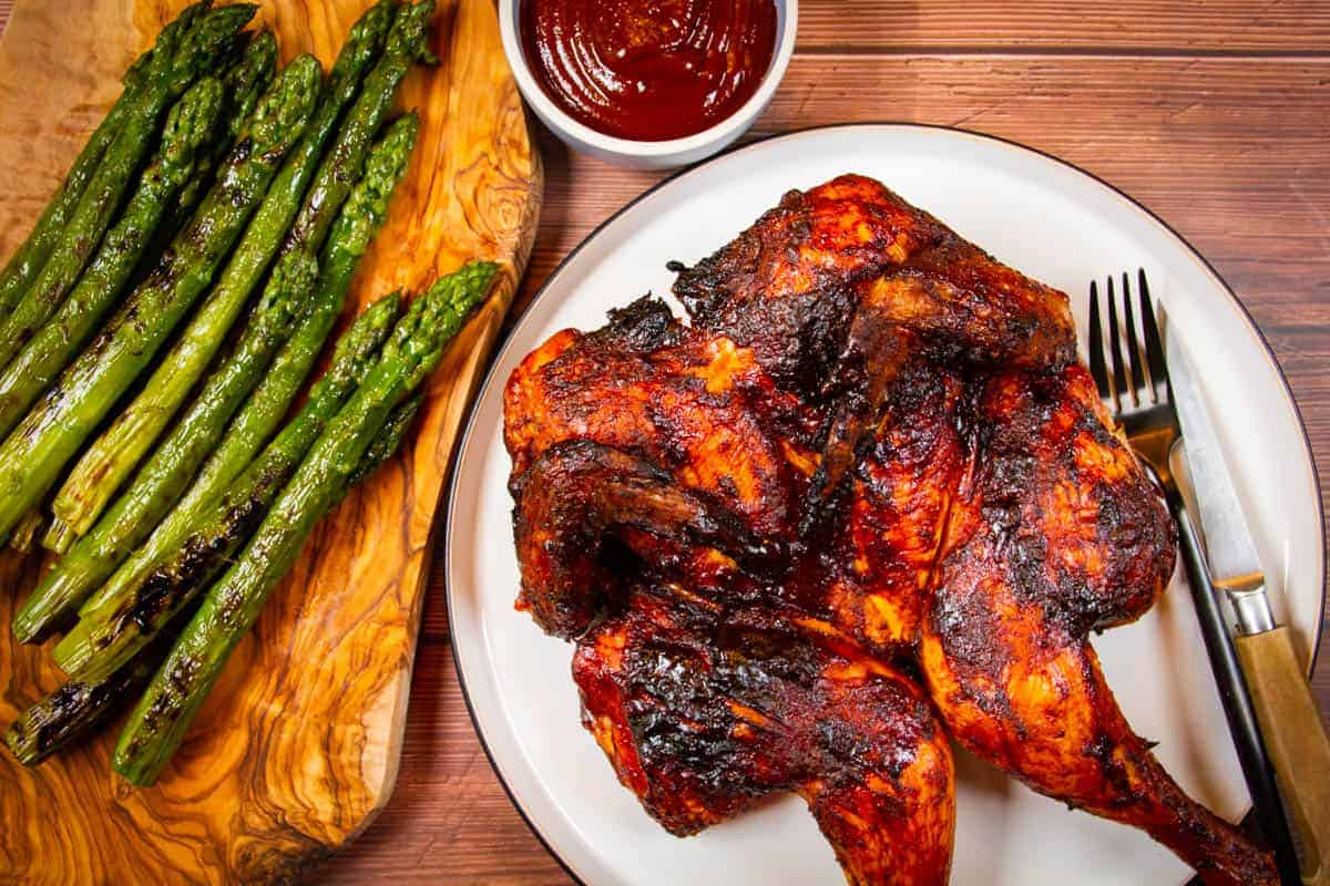 A grilled spatchcock chicken with asparagus and bbq sauce on the side.