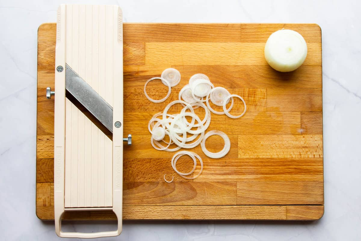 Slicing the onions on a mandoline very thin.