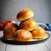 Super soft homemade hamburger buns stacked on a plate with tomatoes in the background.