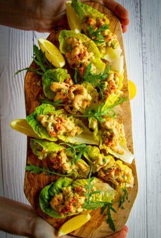 Shrimp salad lettuce cups on a board.