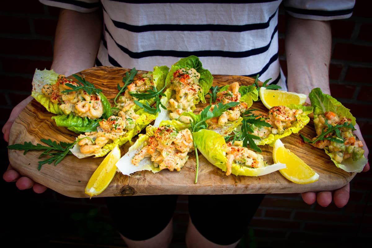 The shrimp salad lettuce wraps being held on a board by a beautiful woman..