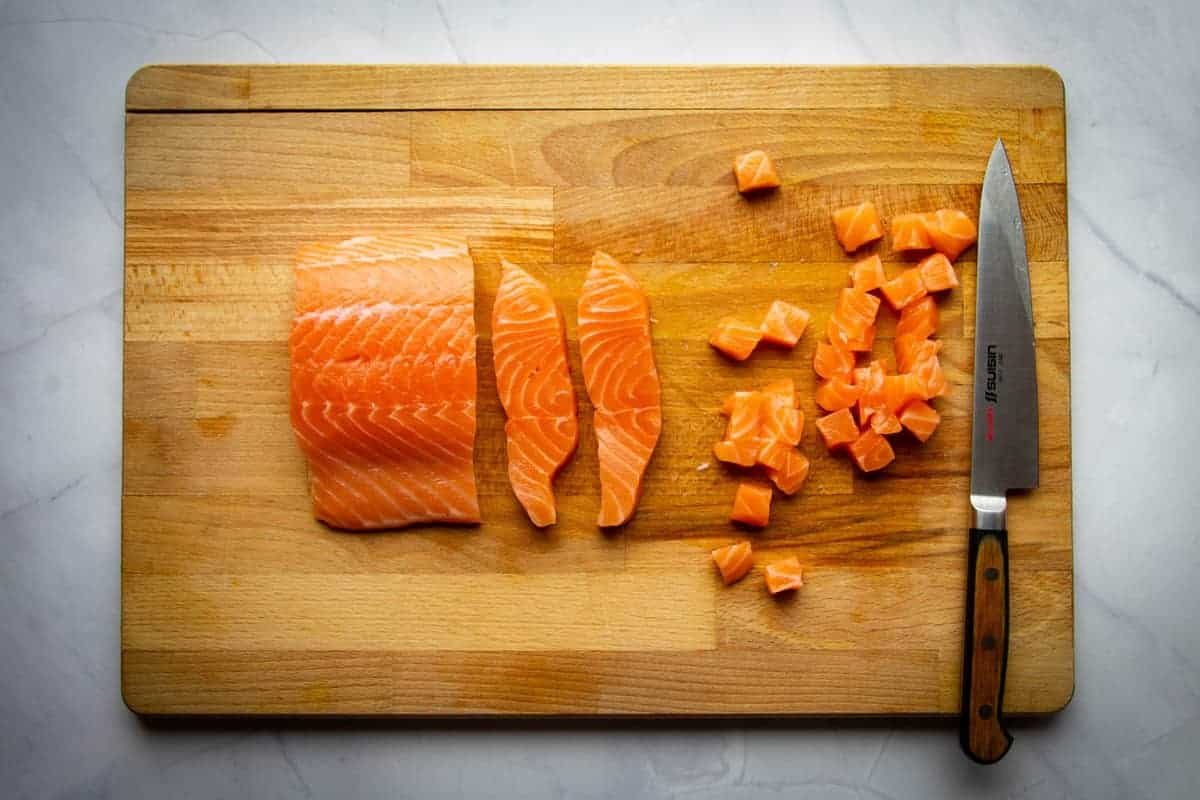The salmon cubed on a board.